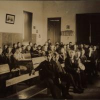 School children and teacher sitting in classroom, undated